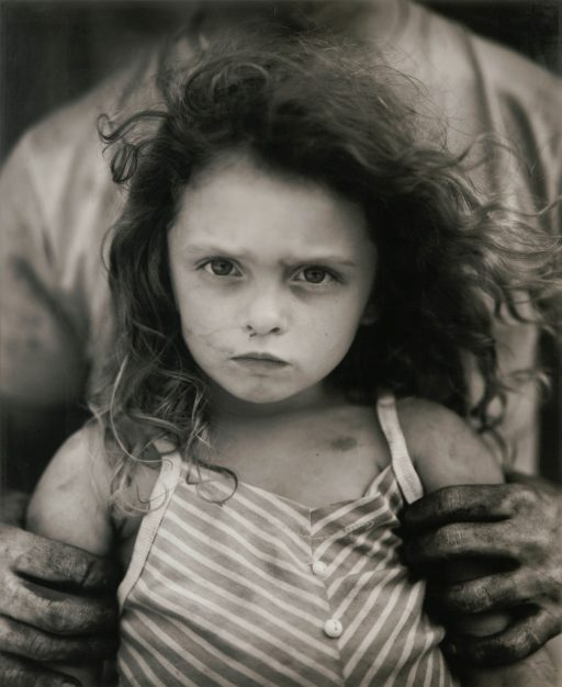 Held by an adult with dirty, weathered hands, a small girl with curly dark hair and a grubby face, stares determinedly into the camera.